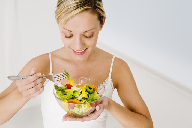 Young Woman Eating a Salad --- Image by © Royalty-Free/Corbis